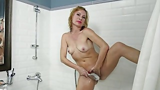 Good-looking MILF is washing her hairy crack